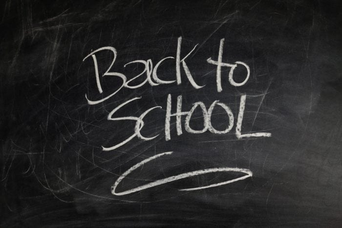 "Chalkboard with the words ""Back to School"" written in white chalk."