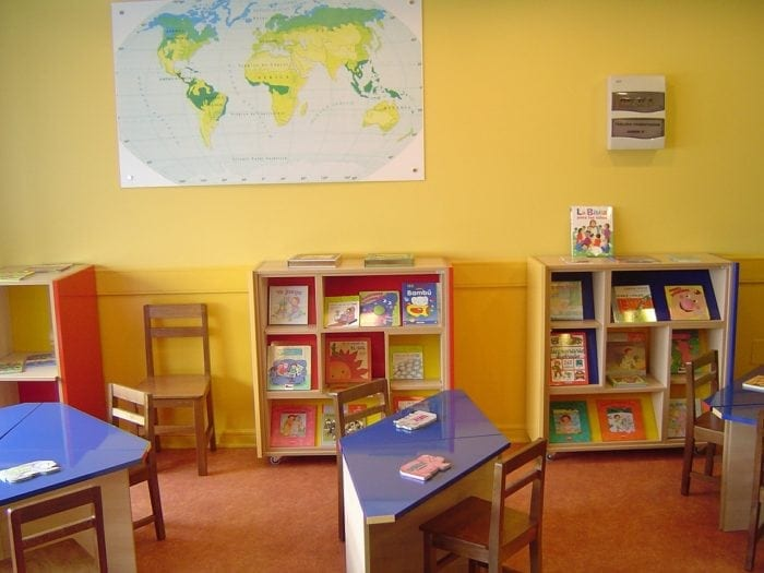 Classroom with small desks and a few bookshelves