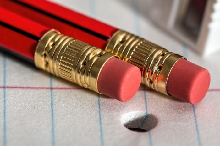 Close up view of two pencil erasers on top of notebook paper.
