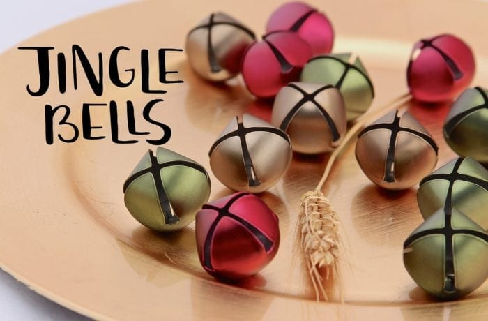 Several jingle bells on a dinner plate.