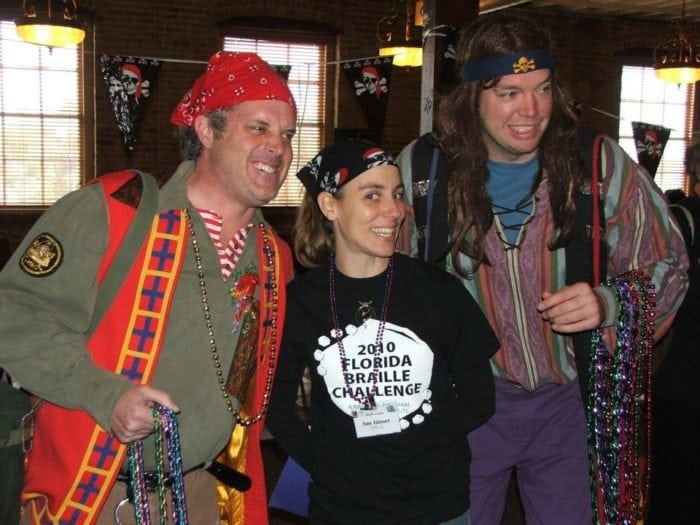Florida Braille Challenge Coordinator Sue Glaser posing for a picture with two men who are dressed in pirate costumes.