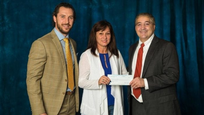 Cheryl Hickman being handed a check by Jeff Vinik and Ryan Callahan of the Tampa Bay Lightning.