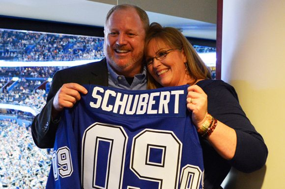 Glen and Kelly Schubert holding a customized Tampa Bay Lightning jersey.