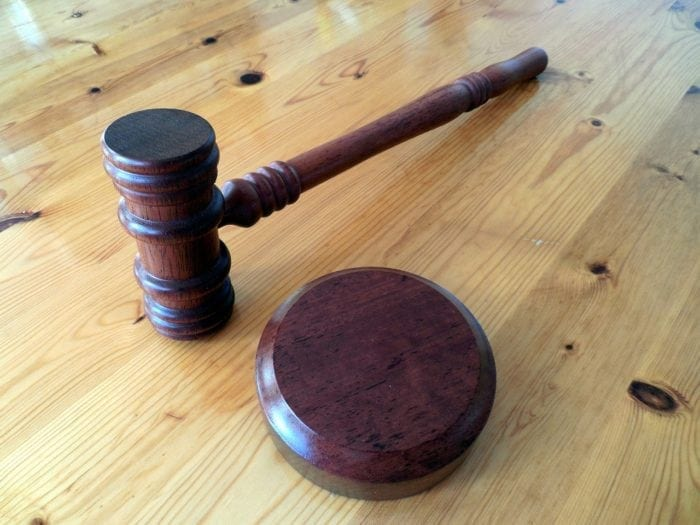 A gavel resting on a wooden table.