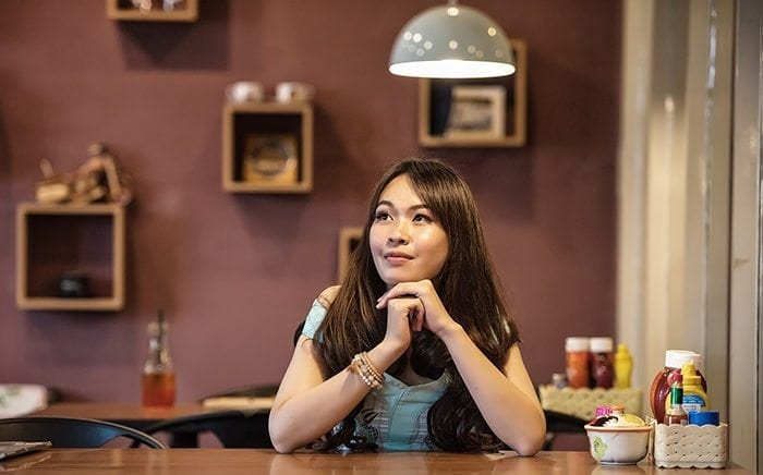 Woman sitting at a table. Her chin is resting on her hands while she thinks.