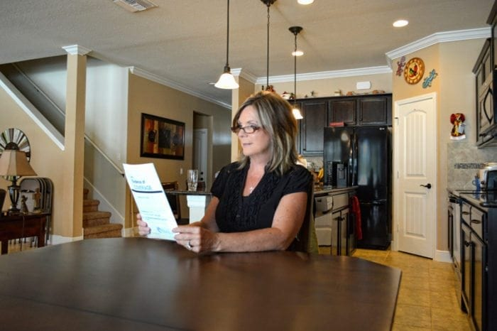 Woman sitting at her kitchen table reading a large print document.