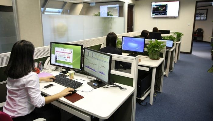Four women sitting at their desks working on computers and laptops.