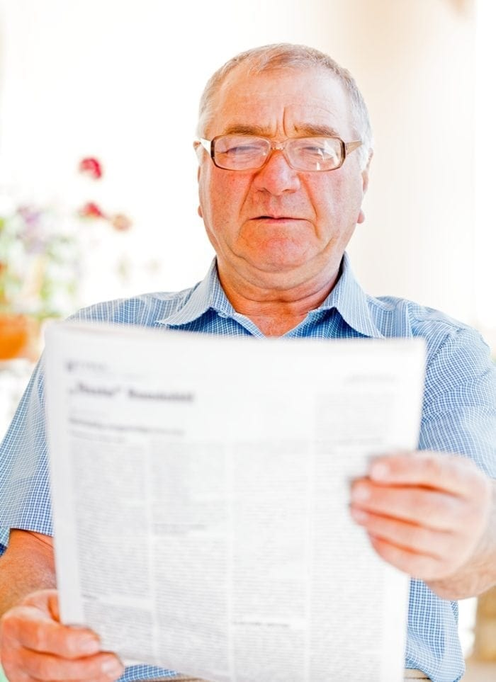 A man struggling to read a print document.