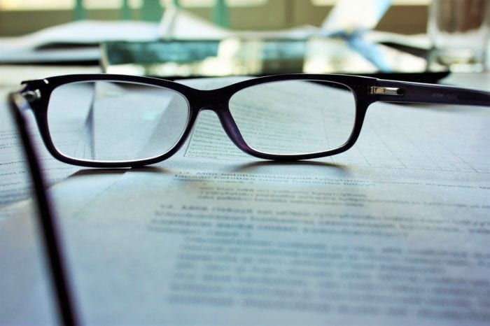 A pair of glasses resting on top of print documents.