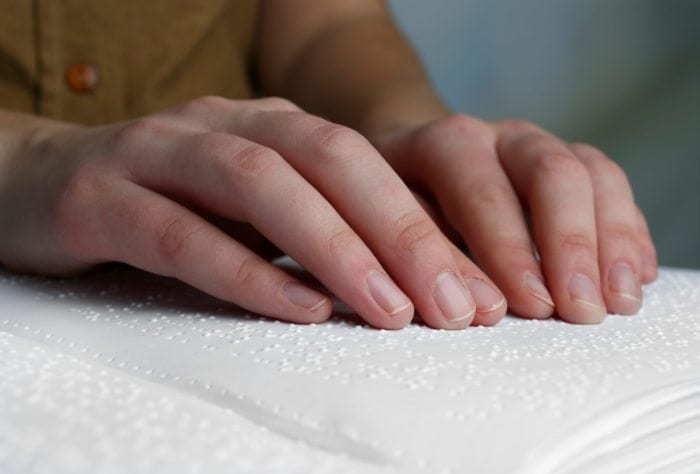 Close up view of someone reading a braille book.
