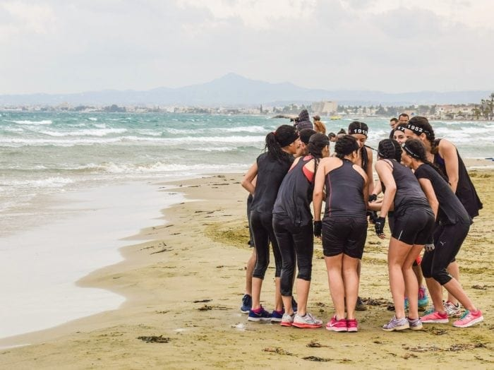 group of runners on a seaside beach standing in a circle doing a team handshake