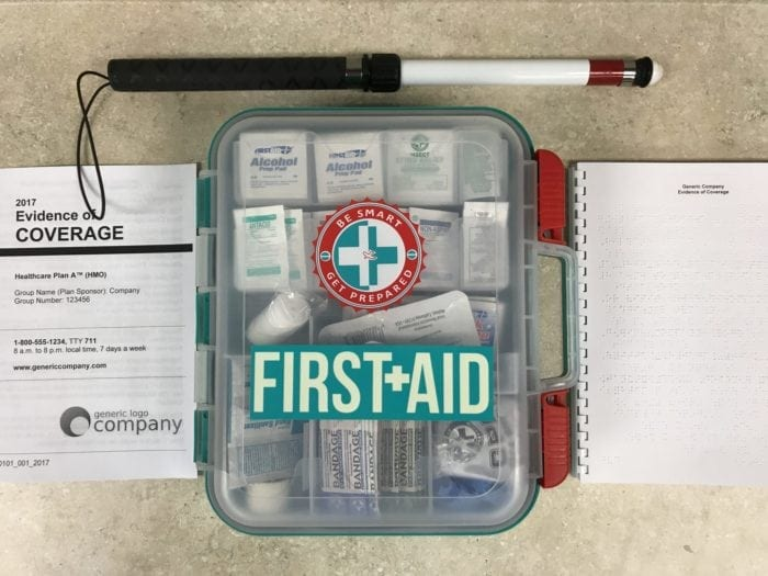 Braille and large print Evidence of Coverage documents on a counter top with a first aid kit and a white cane.