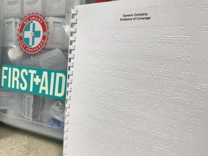Braille Evidence of Coverage document and a first aid kit