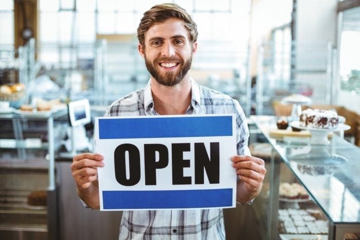 """business owner holding """"open"""" sign"""