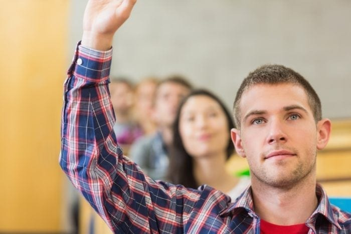 male student raising hand for test