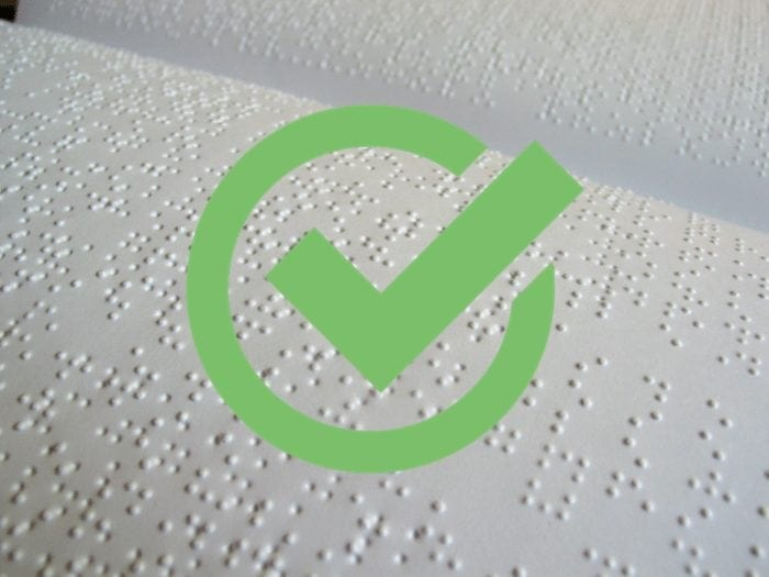 Braille with green checkmark over it