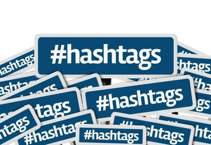 """pile of blue signs with the word """"#hashtags"""" written on them"""