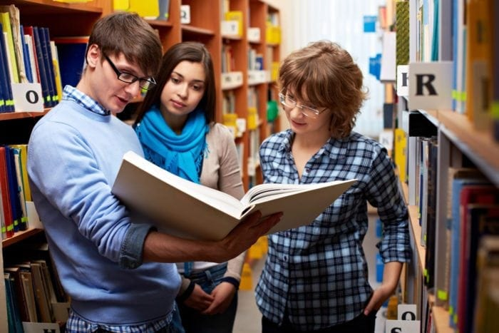 college students looking at a library textbook together