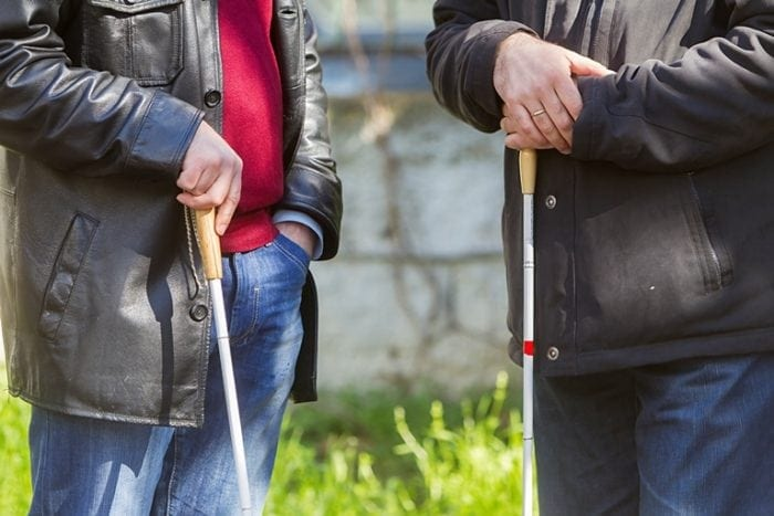 The torso's of 2 people standing outside, each holding a white cane