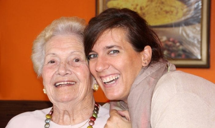 daughter and elderly mother sitting together with big smiles on face