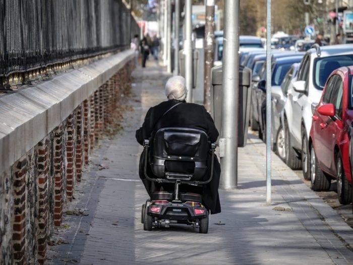 elderly woman in a wheelchair riding away