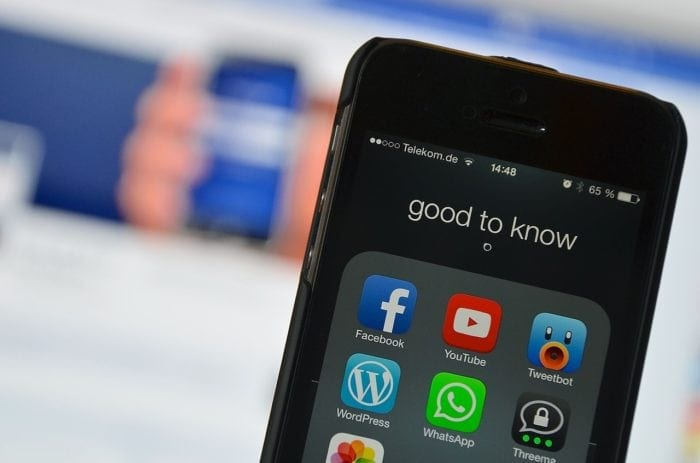 close-up of an iPhone with social media apps on the screen