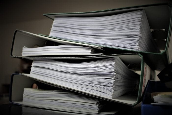 A stack of binders full of legal proceedings.