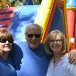 Three people standing in front of a large inflatable obstacle course