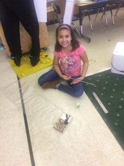 Female student using a ruler and wood sticks to build her Odyssey of the Mind project.