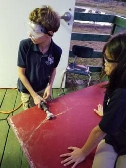 Two student prepping their wood and drawing out their cuts.