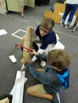 Two male students use a hand saw to cut into a circular block of wood.