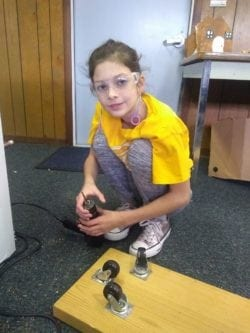 Female student holding drill and attaching wheels to board.