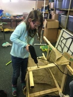 Female student holing a drill and building her project.