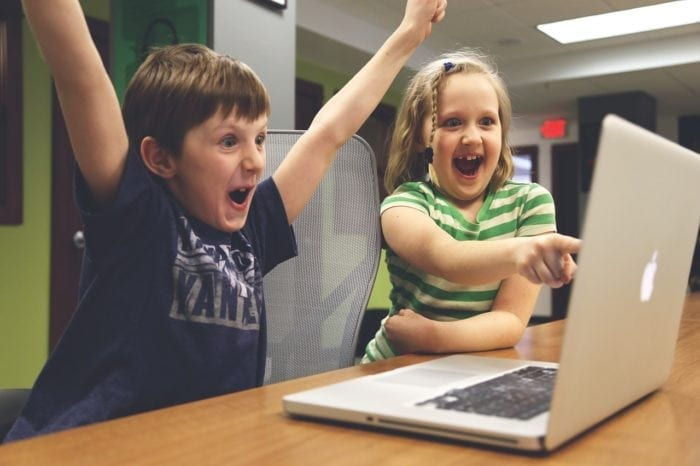 Students yelling with excitement and looking at laptop screen.