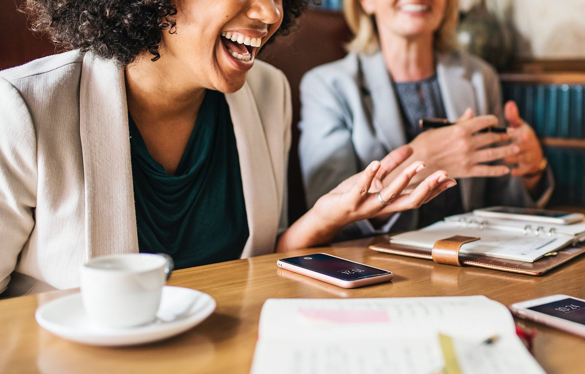 Women laughing while sitting at a table with a cup of coffee, phone and notebooks