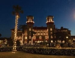A large Spanish-style building, palm trees and bushes covered in white Christmas lights.