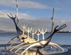 A large Icelandic sculpture in front of a lake.