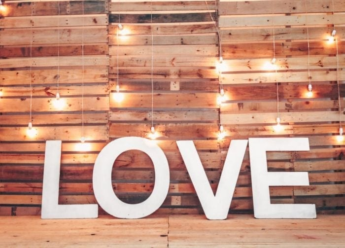 "Large letters spelling ""love"" surrounded by wooden pallets and light bulbs"