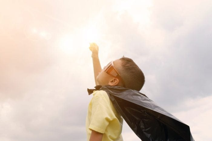 Young boy wearing a plastic bag cape and goggles holding his fist to a cloudy but bright sky
