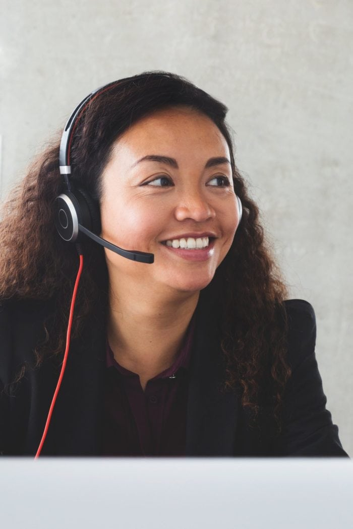A smiling customer service associate with a headset.