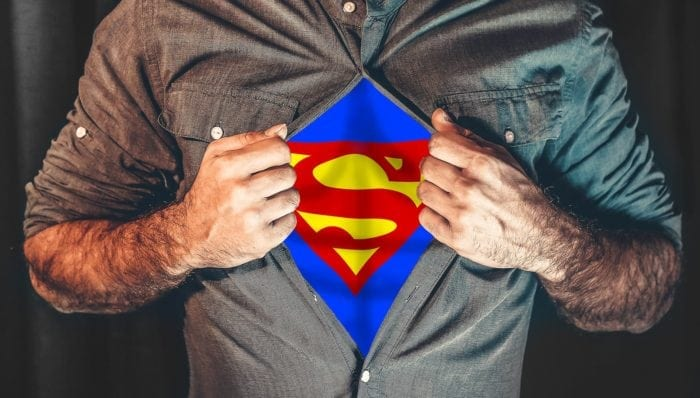 Man's torso with shirt unbuttoned to reveal the Superman logo