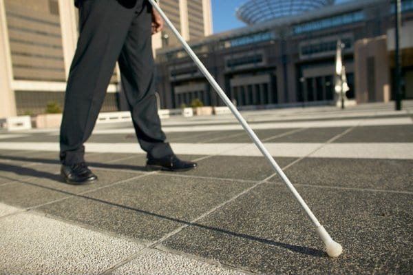 Person walking around with white cane in hand