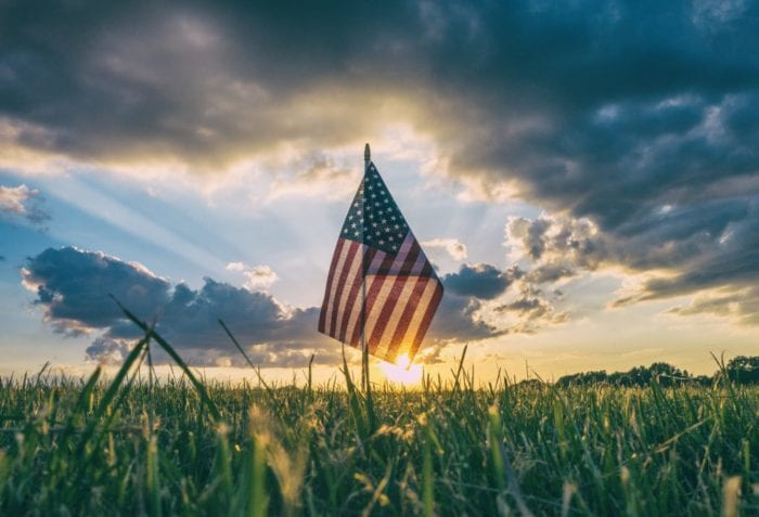 American flag in a field of grass in front of a sunrise.