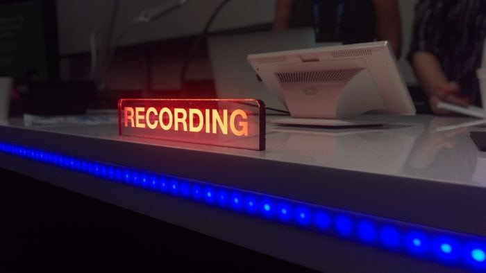 "A recording booth in session with the ""recording"" sign illuminated"