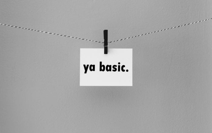 "Note card with the text ""ya basic."" held on a string by a clothespin"