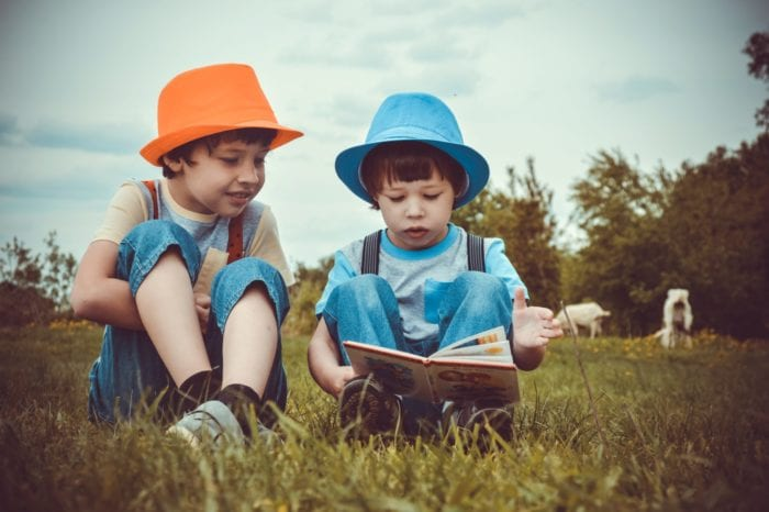 Two young boys sitting in a field with one reading to the other