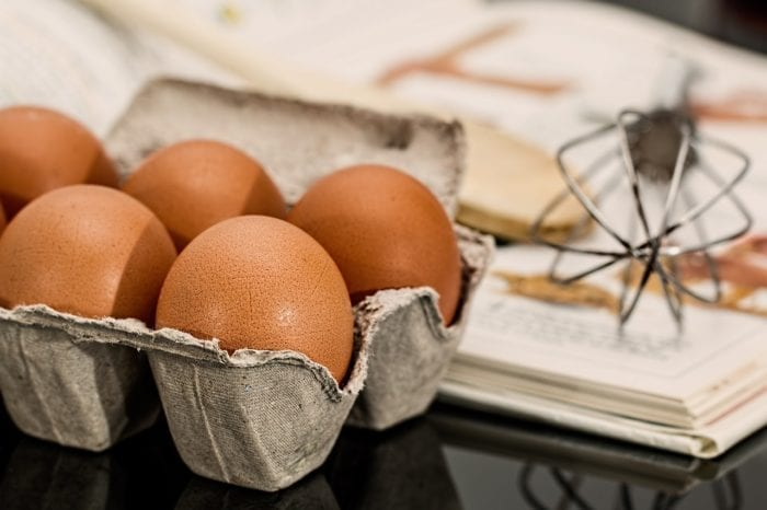 a carton of eggs, a recipe book, and a whisk on the counter