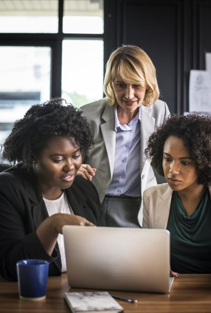 a group of businesswomen standing around a laptop and exchanging ideas