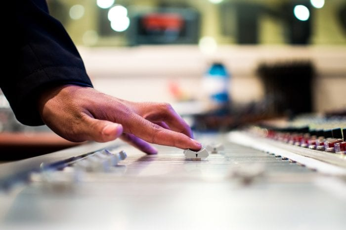 a hand turning the volume on a recording studio mixing desk