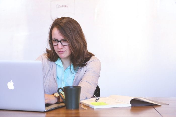woman sits at her desk with a laptop, notebook, and coffee ready to do research on legal matters